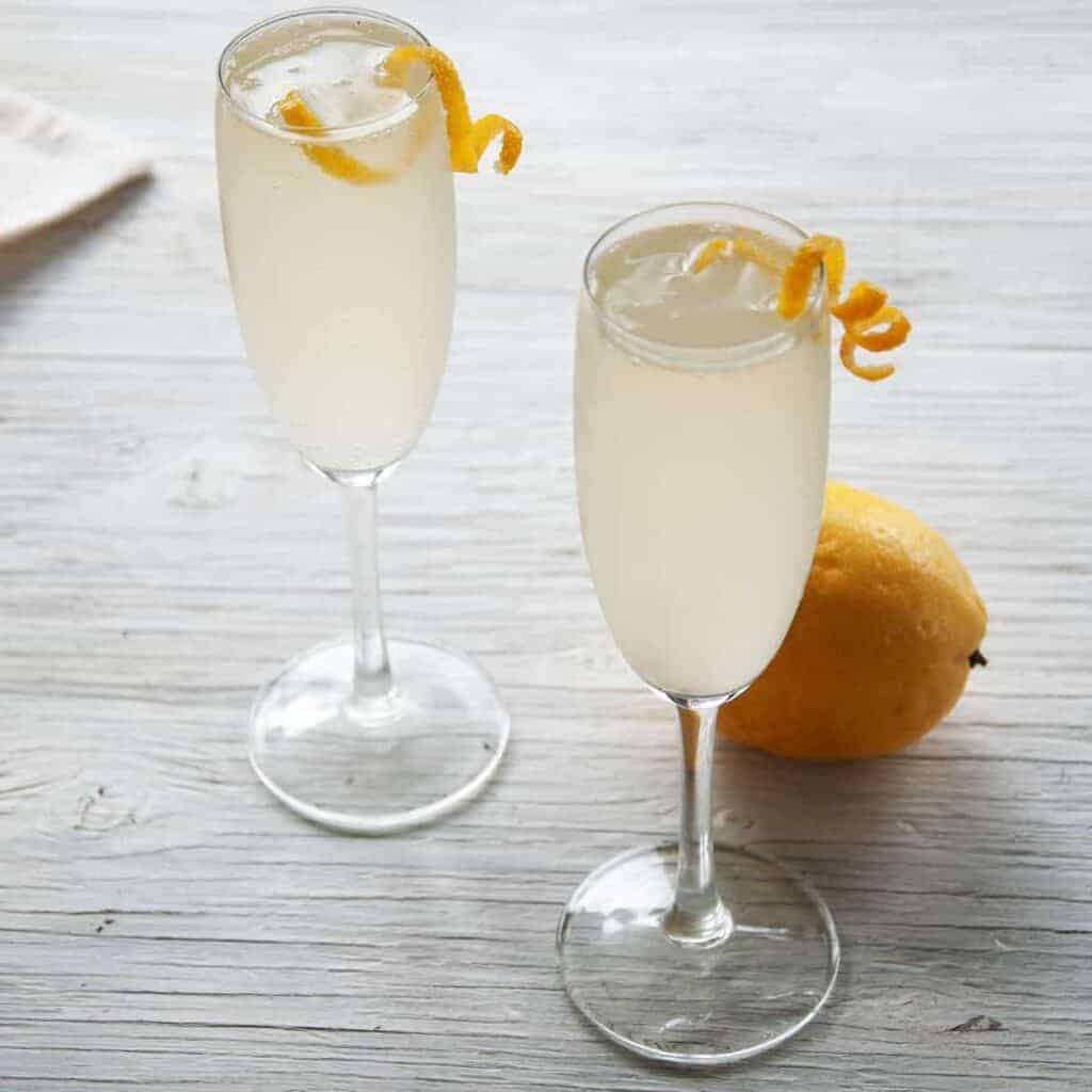 Two French 76 Cocktails on a white table with lemon peel garnish and a whole lemon in the background.