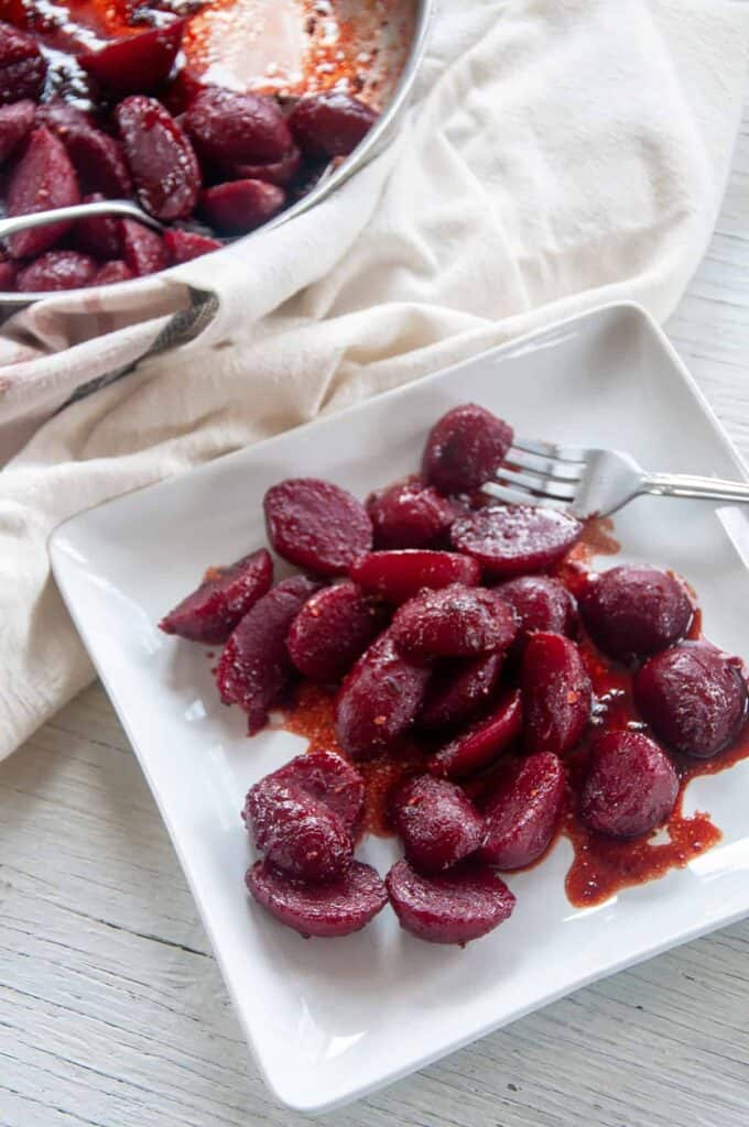 Fried Beets on a square white plage with a frying pan in the background.