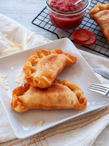 Two fried Italian Panzerotti on a white plate with a fork to the side.