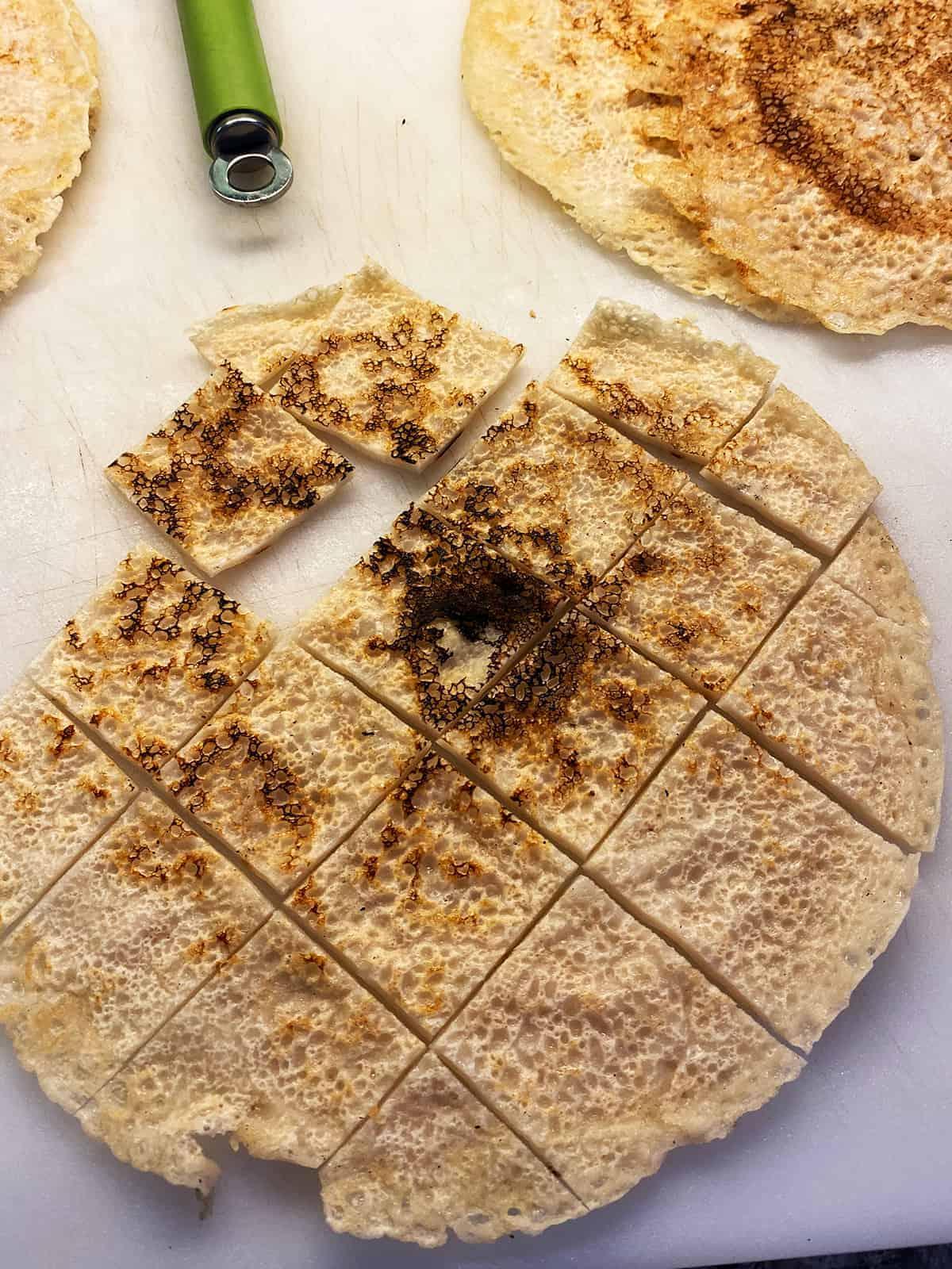 A sheet of testaroli that has been cut with a pizza cutter.