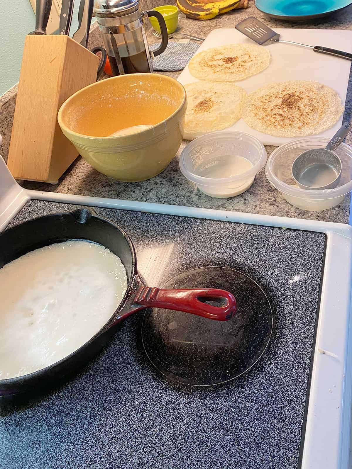Testaroli frying in a cast iron pan and the batter setup off to the side.
