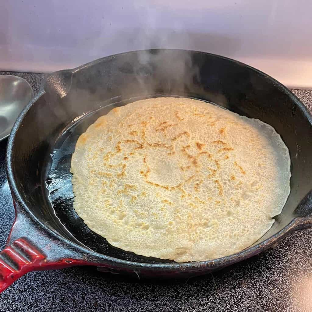 A single testaroli cooking in a cast iron, after having been flipped.