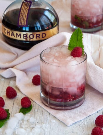 Two Raspberry Gin Smash Cocktails, garnished with mint, on a white table that has raspberries laid across it and a bottle of Chambord.