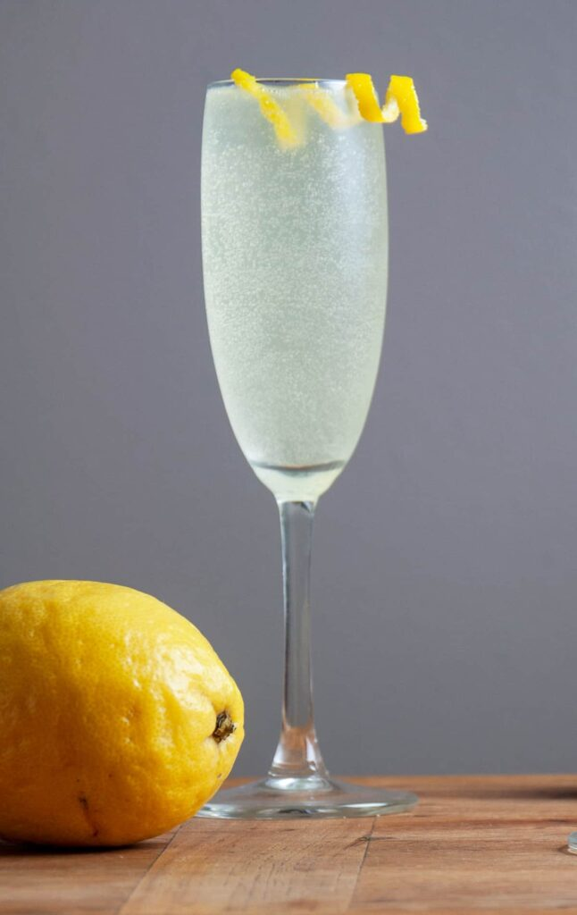 A single French 76 cocktail on a butcher block board and a lemon to the side.