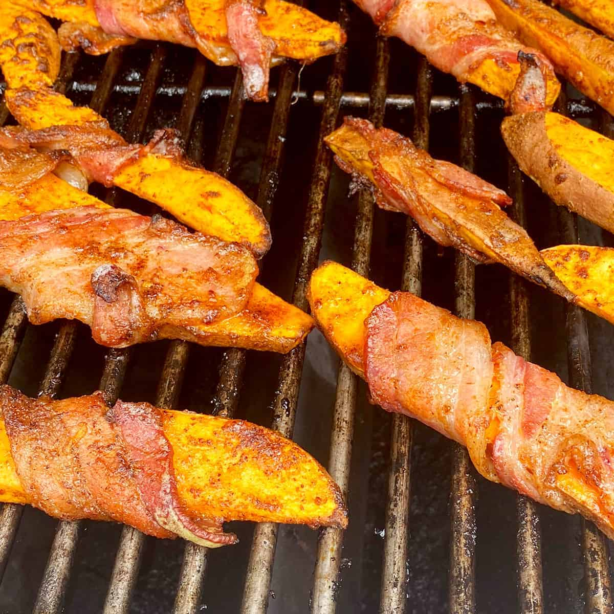 Bacon-wrapped sweet potato fries on the grill cooking.