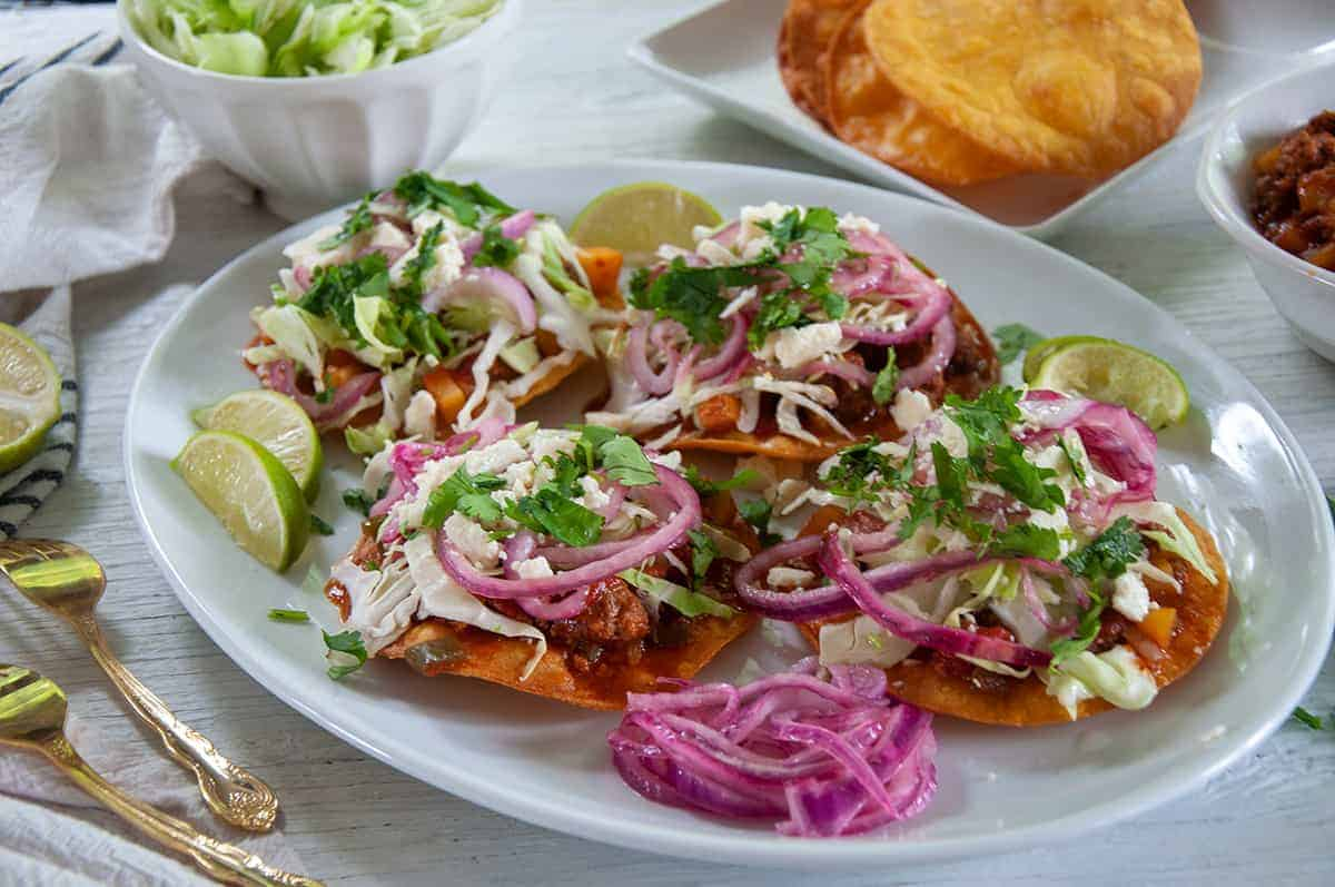 A big white platter full of Honduran Enchiladas, red pickled onions, and limes on the side.