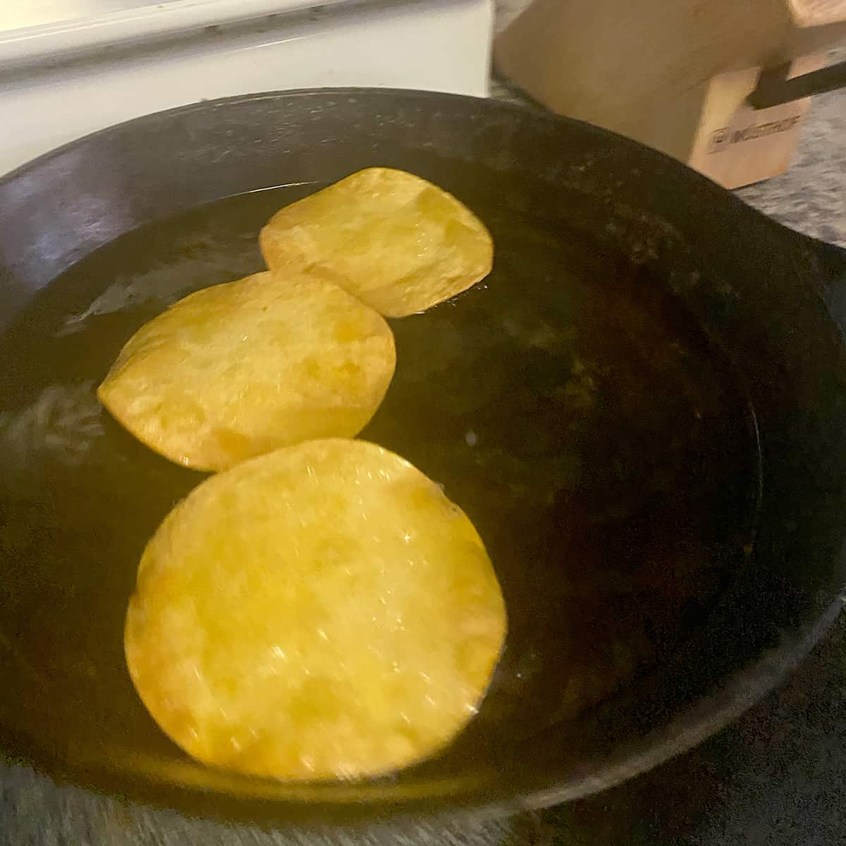 Three corn tortillas frying in hot oil in a cast iron pan.