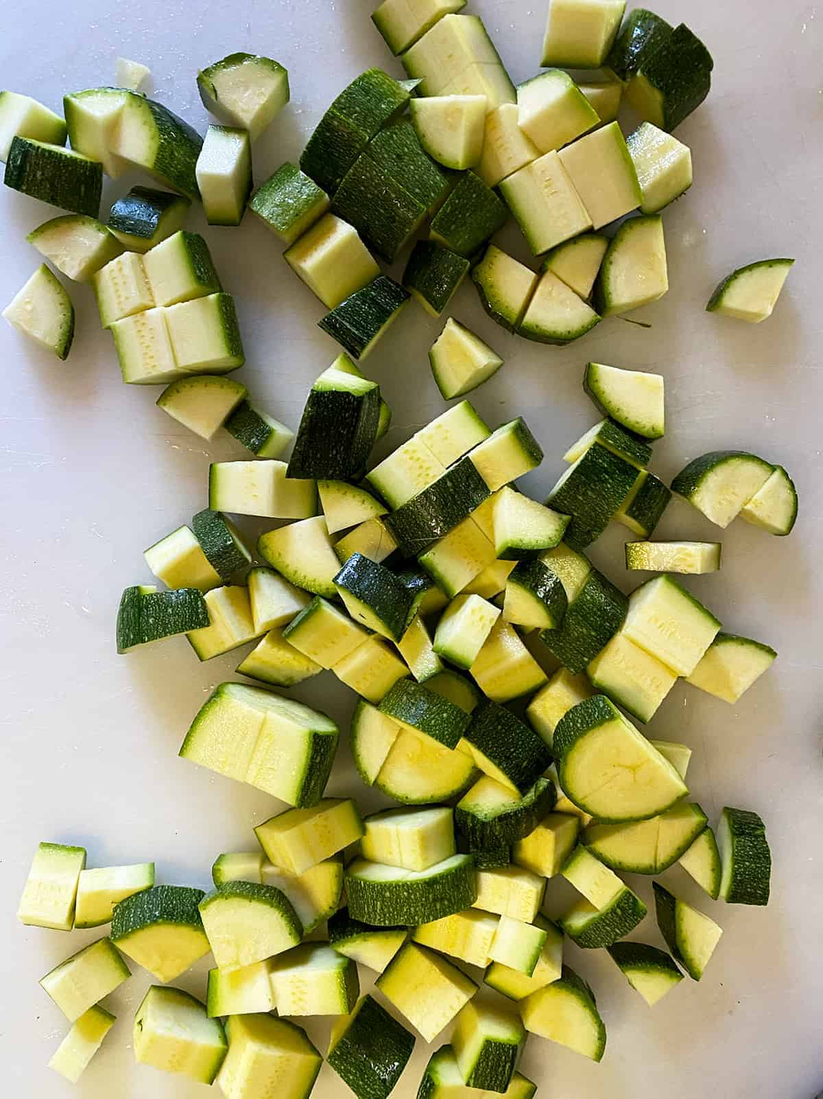 Chopped zucchini on a cutting board.