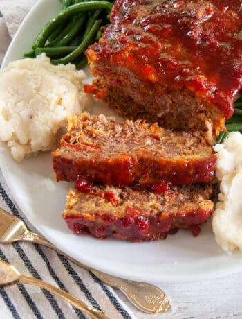Spicy Italian Meatloaf on a big platter with mashed potatoes and green beans.