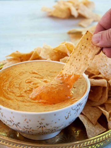 Homemade Queso Dip in a white and gold bowl and a hand dipping a single corn chip into it.