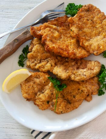Four Pork Schnitzel cutlets on a large white platter, garnished with parsley and lemon.