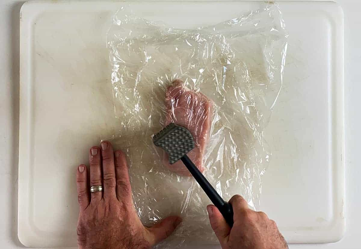 One trimmed pork chop between two sheets of plastic wrap and a meat tenderizer being held in a hand just prior to striking the chop.