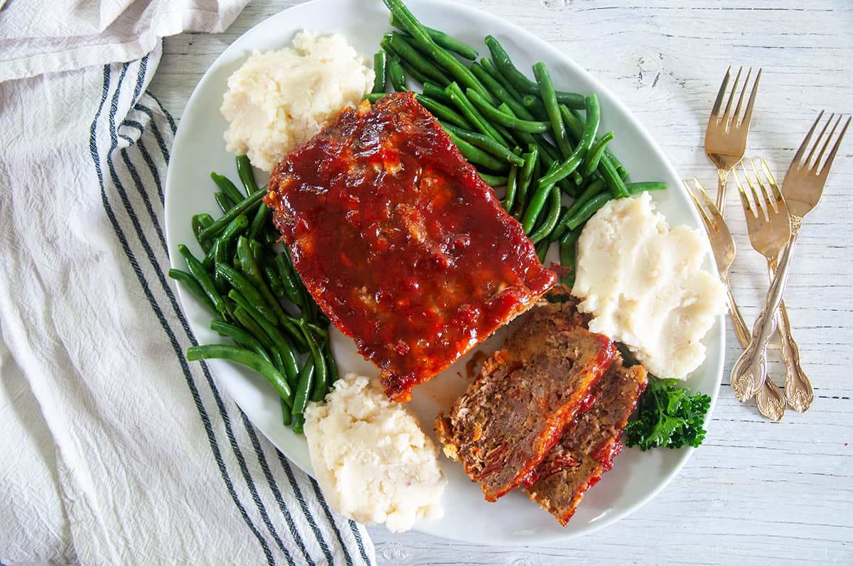 Full platter of Italian Meatloaf with beans and potatoes on the side.