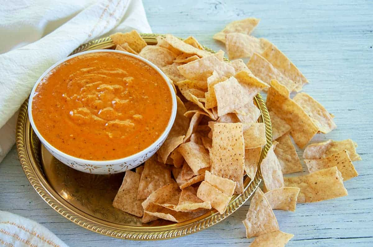 Bowl of queso dip on a gold platter with corn chips spread all around the platter and the table underneath.