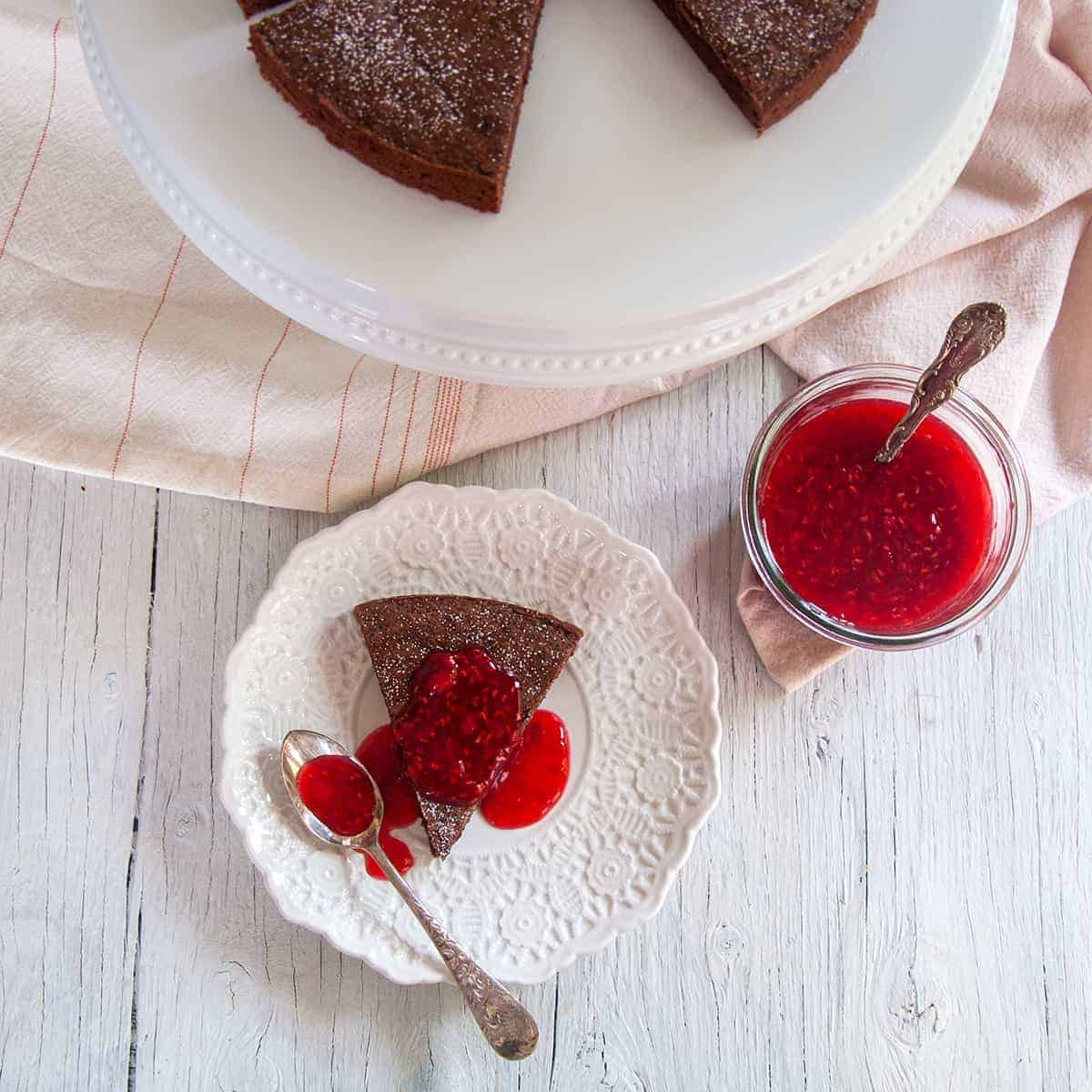 One slice of our Kladdkaka Swedish Sticky Cake on a white plate, covered in raspberry topping and a spoon to the side.