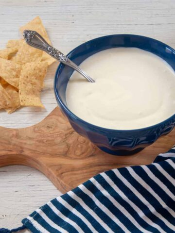 Bowl of homemade sour cream in a blue bowl that rests on a cutting board and chips.