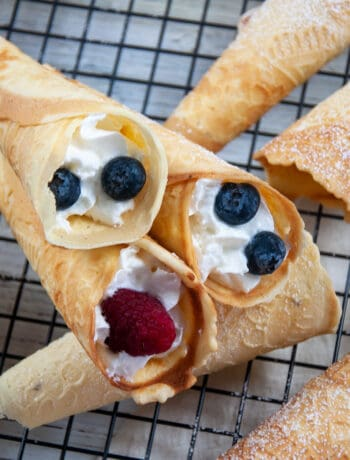 Three Krumkake filled with whipped cream, blueberries, and raspberries that are laying on top of several unfilled ones that have been sprinkled with powdered sugar.