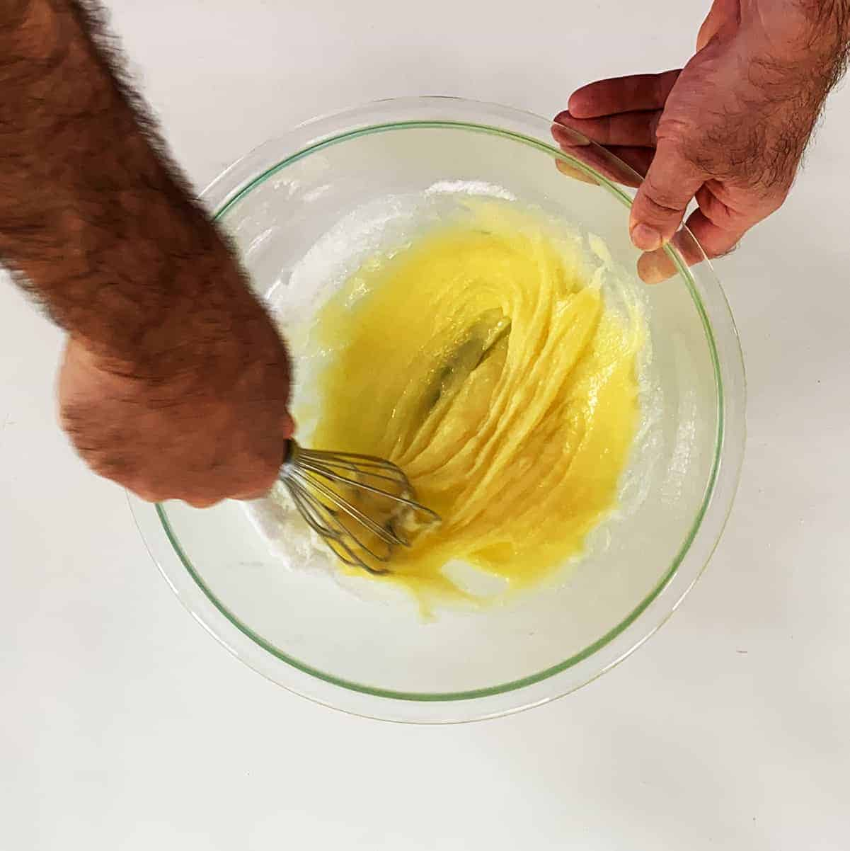 Mixing egg, sugar, and vanilla together in a large glass bowl with a beater.