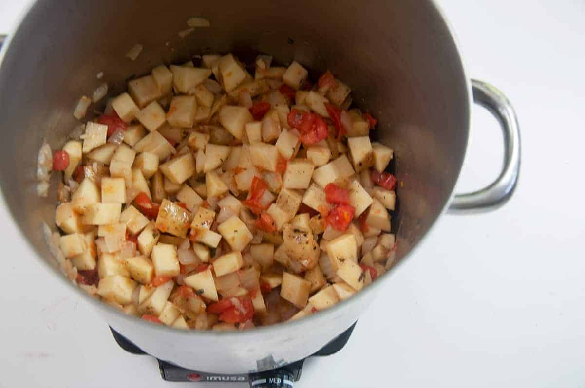 Pot of potato, onion, tomato, and oregano cooking over medium heat on a white table.