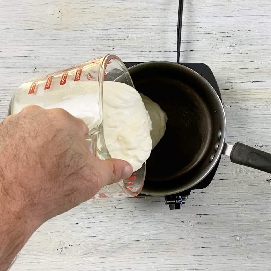 Pouring sour cream into a sauce pan.