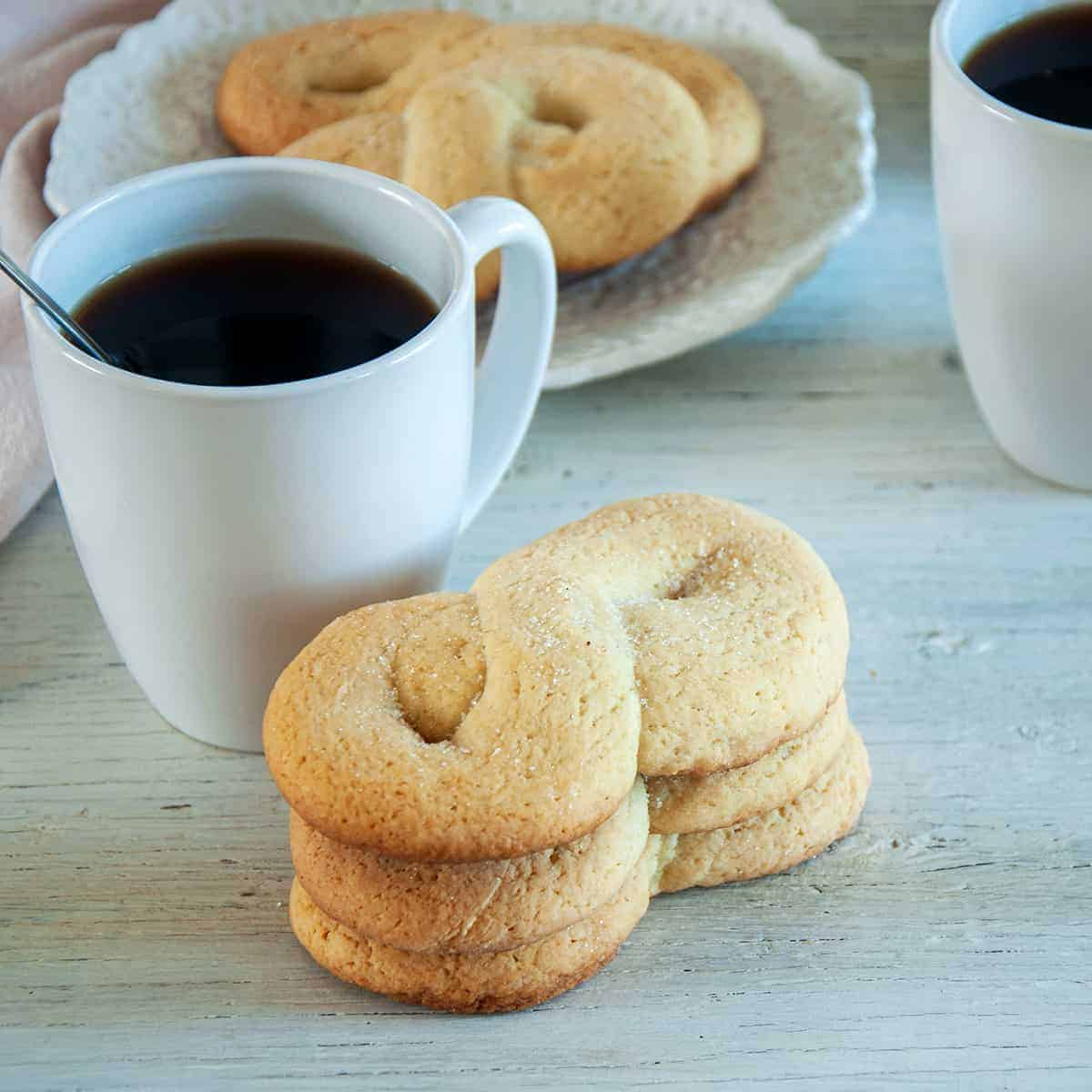 Three kringler cookies stacked on top of each other with a white mug of coffee showing to the side.