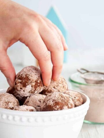 A hand pulling one rum ball out of a bowl full of them.
