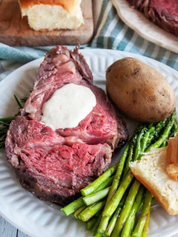 Slice of Prime Rib on a white plate being served with asparagus, a bun, a baked potato, and the entire roast barely showing in the background.