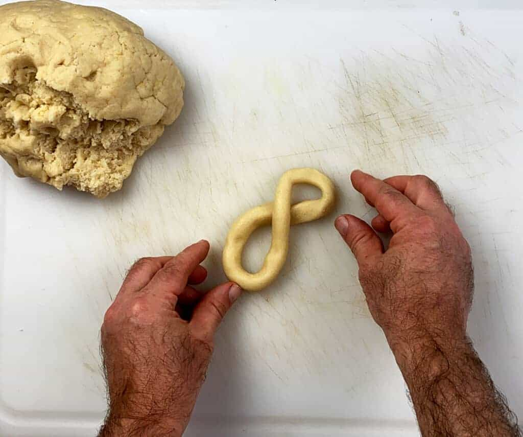 Forming a cookie into the infinity symbol on a white cutting sheet.