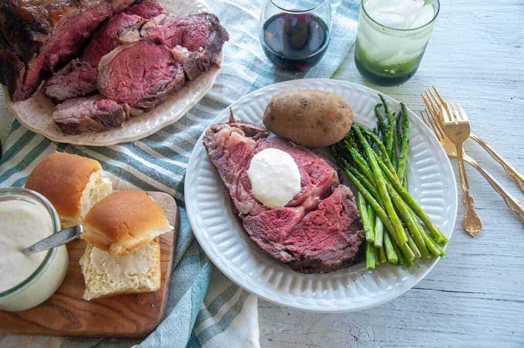 Full Sous Vide Prime Rib layout with a plate of meat, asparagus, potato, and horsey sauce.