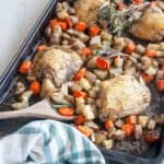 Baked Italian Chicken Thighs on a baking pan with carrots, potatoes, a wooden spoon and fresh rosemary.