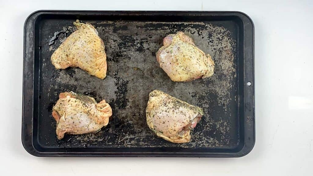 Four uncooked chicken thighs getting ready for the oven.