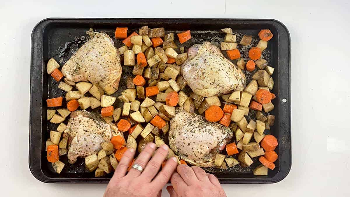 Chicken thighs, potatoes, and carrots all spread out on a baking pan.