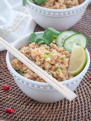 A bowl of Crab Fried Rice in a white bowl that is garnished with cilantro, cucumbers, lime.