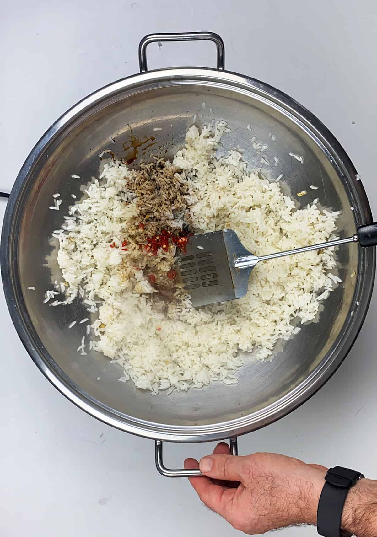 Vigorously stirring rice, pepper, and asian sauces in heated wok.
