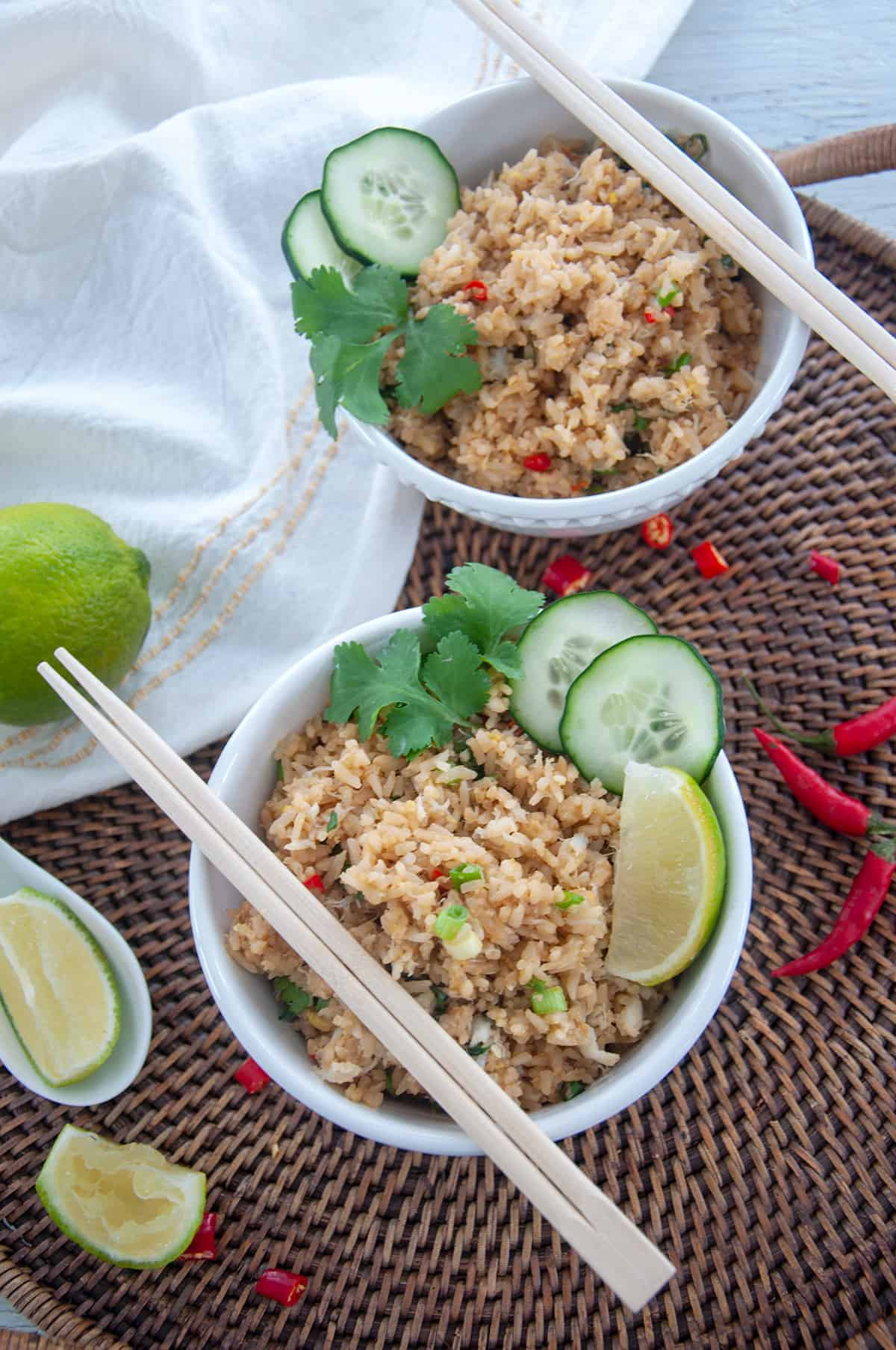 Crab Fried Rice in two white bowls with lime and green onions off to the side. This bowl is sitting on a wicker tray that has a spent lime wedge, thai chili peppers, and a whole lime.