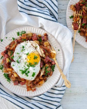 Corned Beef Hash on a white plate with a single sunny side up egg on top.