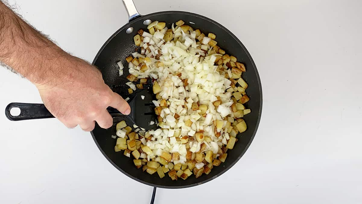 A hand stirring potatoes and onions.
