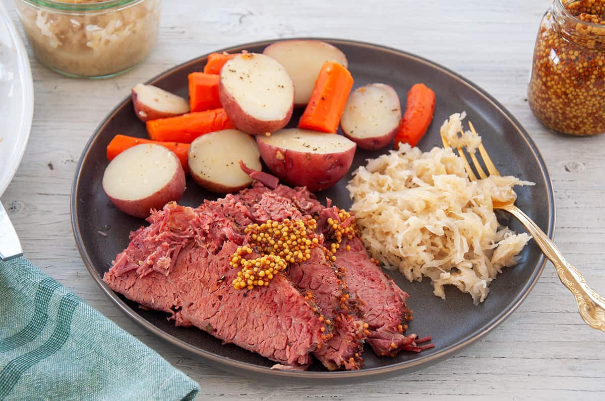 Corned Beef cuts, covered with whole grain mustard, and potatoes, carrots, and sauerkraut on the side of a plate.