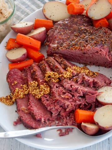 Full sous vide corned beef roast on a large serving platter with potatoes and carrots all around the sides of the roast.