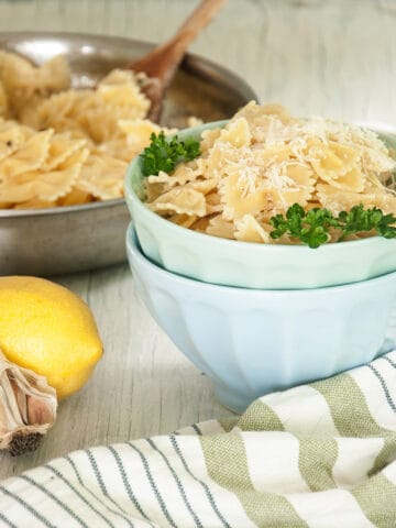 Creamy Lemon Pasta over Farfalle in a light blue bowl and the entire dish right behind it.