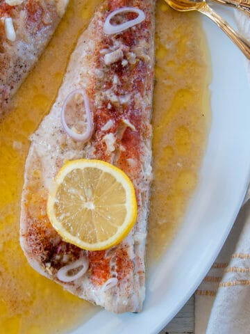 One baked walleye filet with a lemon slice on top and sitting in white wine sauce and gold forks to the side.