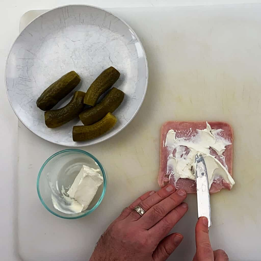 Spreading cream cheese on the ham with pickles and cream cheese on the side.