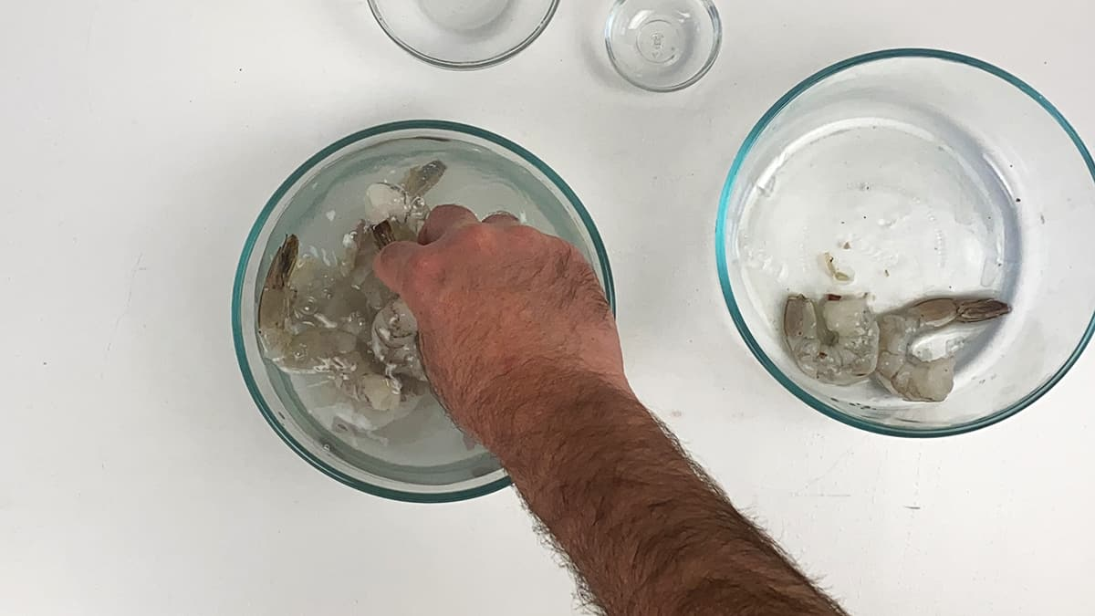 A hand placing raw shrimp into a bowl full of water, sugar, and salt.