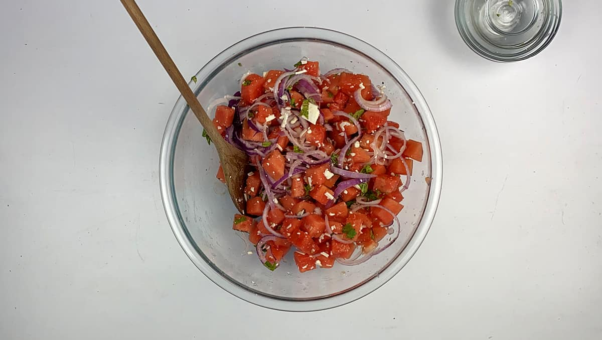 Mixing all of the ingredients in our watermelon feta salad before adging the balsamic vinegar.