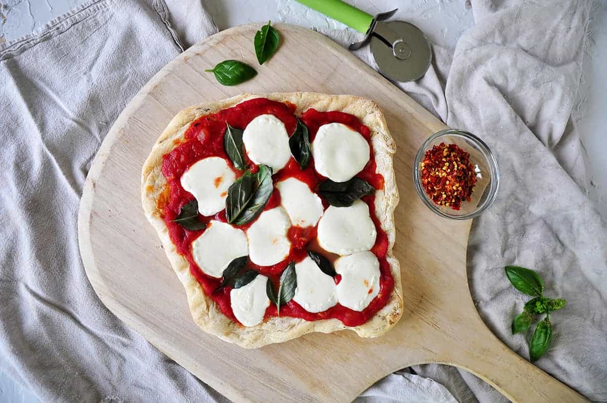 Full weber pizza on a wood pizza peel with basil and red pepper to the side.