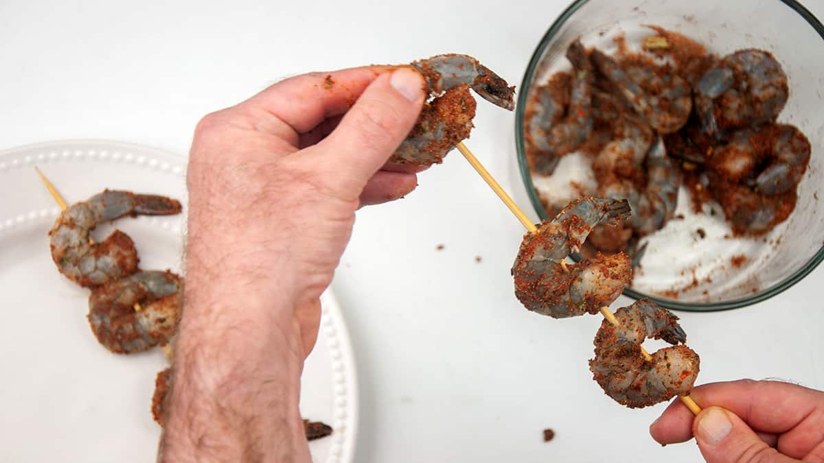 A hand skewering a shrimp on a wooden skewer that already has two on it.