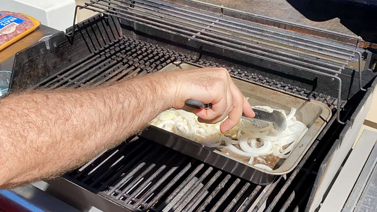 Using a pair of tongs to mix onions around in a baking dish.