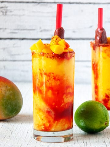 Two Mangonadas with Tamarind candy straws on a white table with a mango and lime.