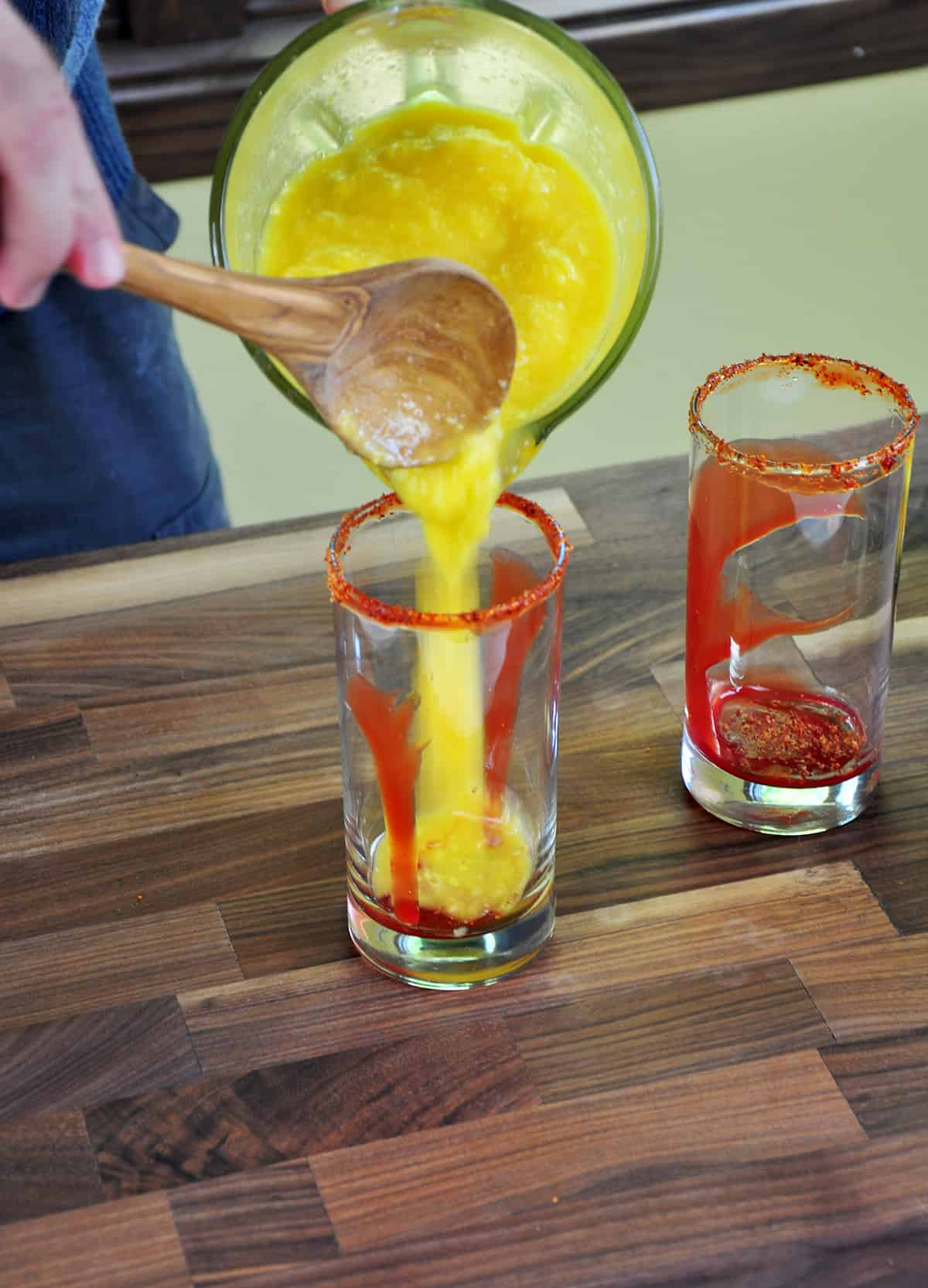 Pouring Mango mixture into a glass that has already been rimmed and has chamoy in the bottom.