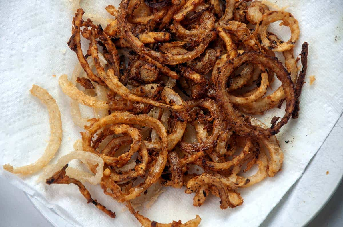 Fried onion on a paper towel-lined plate.
